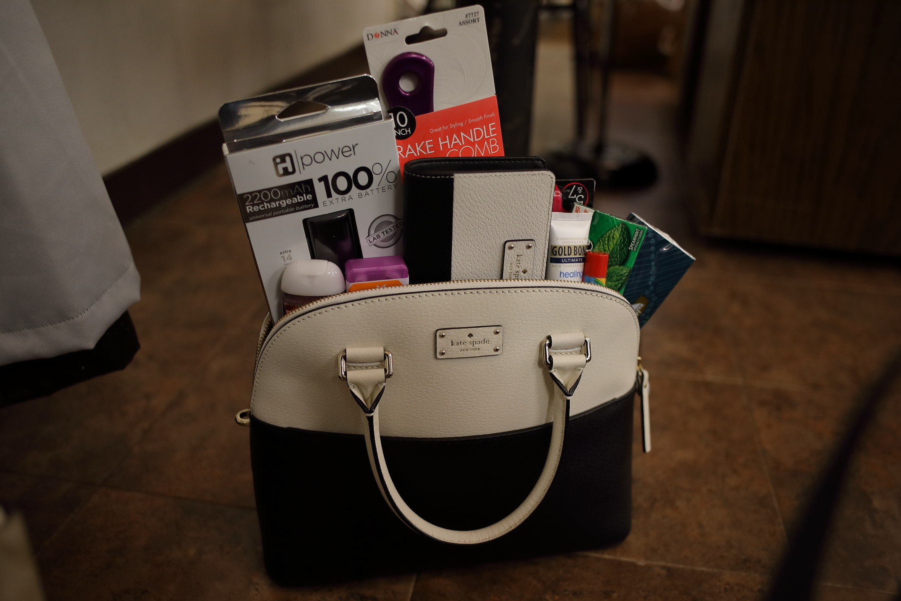 Black and white Kate Spade bag with portable powerbank, wallet, and personal care items such as lotion, comb, and gum.