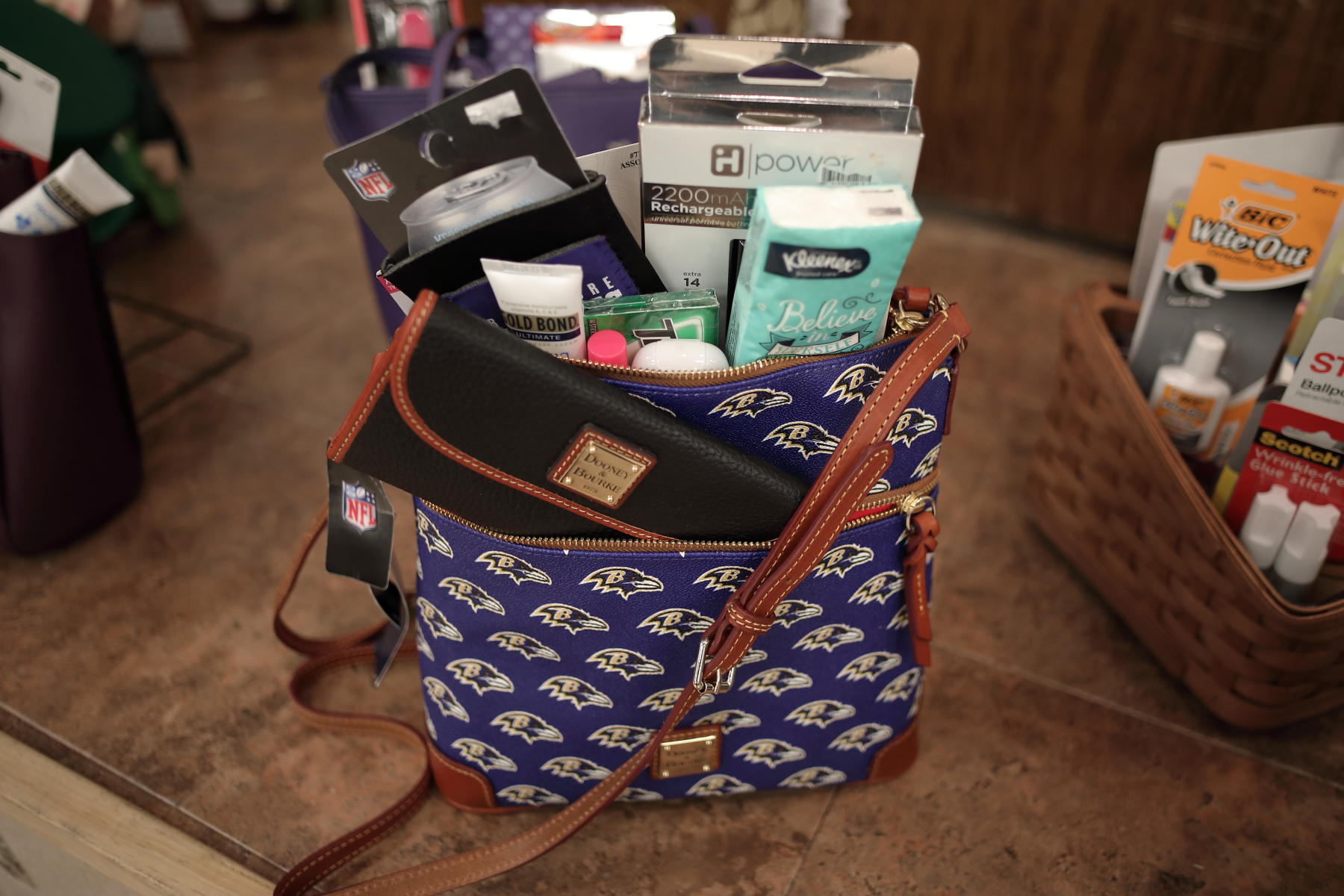 Dooney & Bourke Ravens handbag with a portable powerbank and personal items such as lotion, lip balm, and gum.