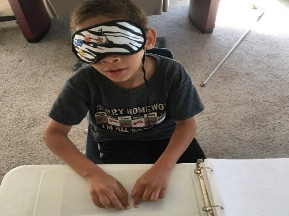 shows a boy in sleep shades reading the Braille letter he just received in the mail.